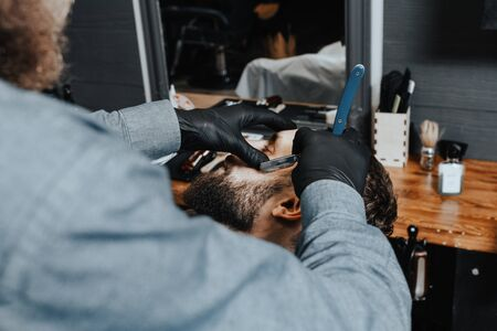 BARBERSHOP THEME. BEARDED BARBER IN BLACK RUBBER GLOVES IS TRIMMING THE BEARD OF HIS YOUNG HANDSOME CLIENT. HE IS USING A STRAIGHT RAZOR