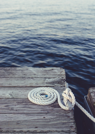 coiled rope: White coiled rope on a dock. Stock Photo