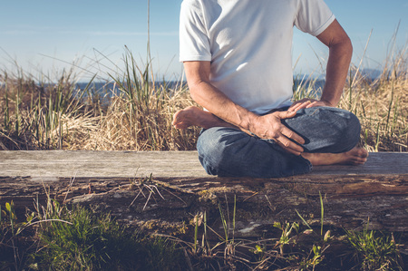 aging brain: Man sitting in relaxing yoga position.