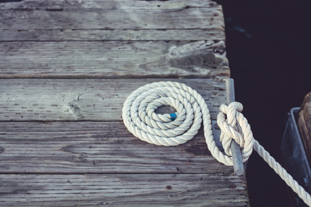 coiled rope: White coiled rope at a dock.