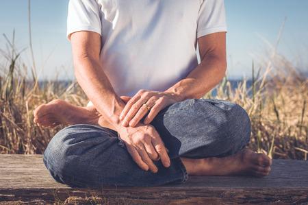 eastern philosophy: Man sitting in Yoga Pose. Stock Photo