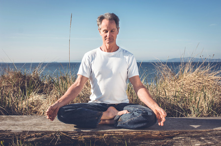 aging brain: Man sitting in Yoga Pose. Stock Photo