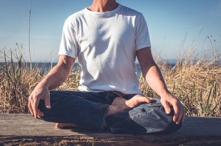 brain aging: Man sitting in relaxing yoga position.