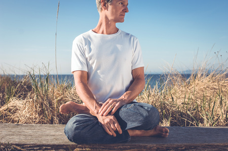 eastern philosophy: Man sitting in relaxing yoga position.