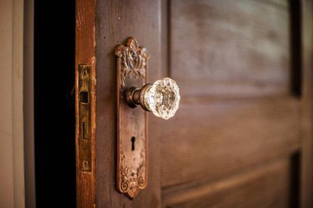 Een verweerde oude houten deur met een sierlijke kristallen deurknop.