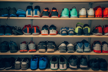 Various styles of worn athletic shoes sitting on a shelf.