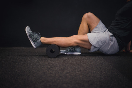 Man using a foam roller on the ground in the gym 版權商用圖片