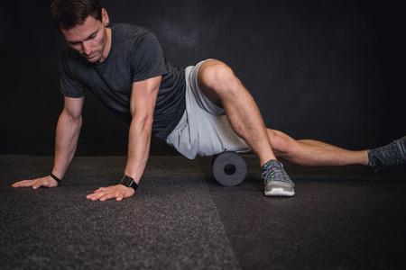 hombre que usa un rodillo en el suelo en el gimnasio