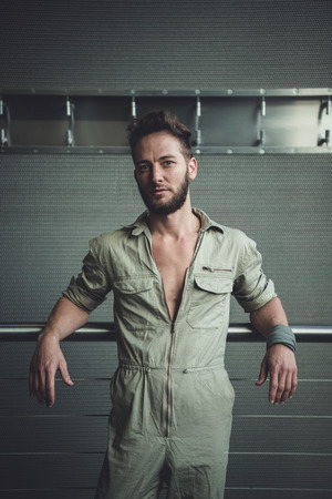 Handsome man in mid thirties wearing a khaki one piece jumpsuit posing. Zdjęcie Seryjne