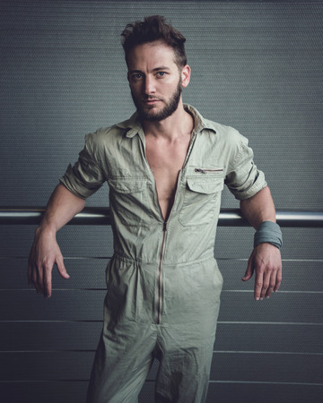 Handsome man in mid thirties wearing a khaki one piece of jumpsuit posing.