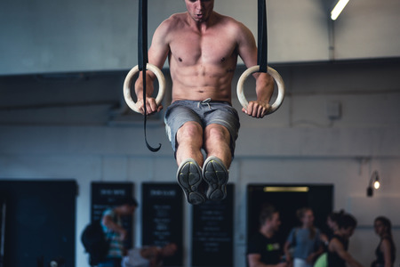 Men performing muscle-ups on the rings in a fitness studio