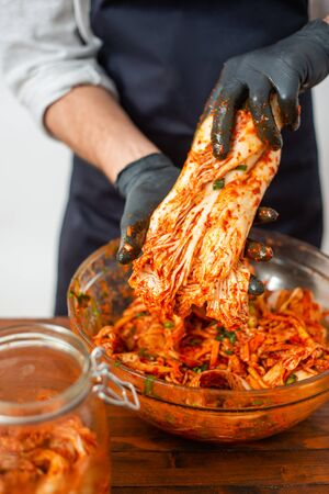 Person making Kimchi wearing black rubber gloves for protection Zdjęcie Seryjne