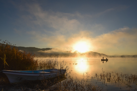 Sunrise at the lake Kawaguchiko,People fishing on a boat,silhouette Stock Photo