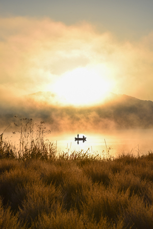 fishing lake: Sunrise at the lake Kawaguchiko,People fishing on a boat,silhouette Stock Photo