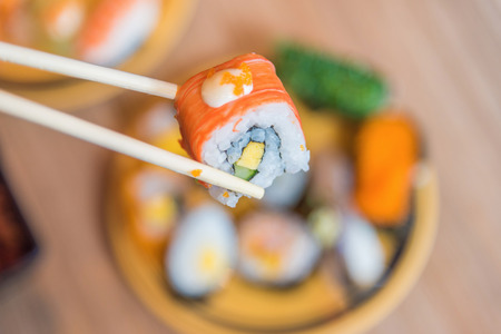 sushi set: Sushi roll : Roll sushi held by chopsticks from background of assorted sushi set