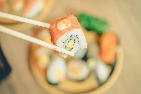 sushi set: Sushi roll : Roll sushi held by chopsticks from background of assorted sushi set ,vintage