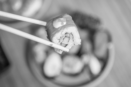 sushi set: Sushi roll : Roll sushi held by chopsticks from background of assorted sushi set , black and white