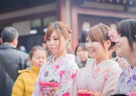 literally: Tokyo, Asakusa. January 25, 2015. girls in japanese typical dress. The kimono is the traditional japanese dress and means literally something to dress