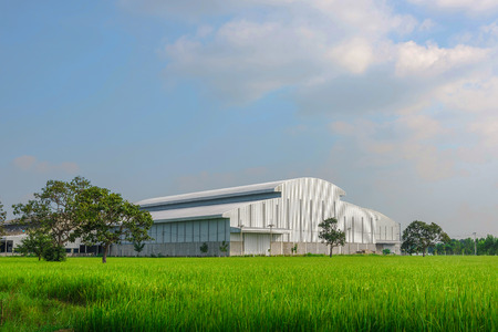 Factory in the middle of a green farmland on a cloudy day 写真素材