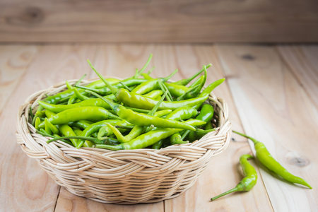 pimiento: Green peppers in wicker basket on wooden background