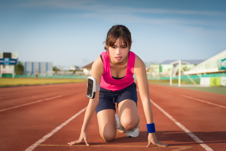 participant: Confident young female athlete in starting position ready to start a sprint. Woman sprinter ready for a run