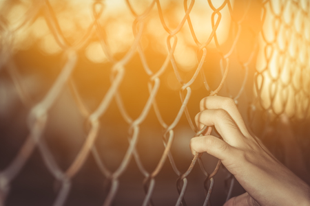 Hand holding on chain link fence,  vintage tone