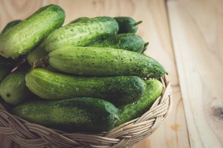 lug: Fresh cucumbers in basket on wood , vintage tone