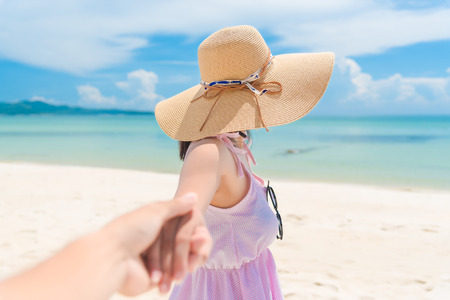 view from behind: Woman walking on romantic honeymoon beach holidays holding hand of boyfriend following her, view from behind.
