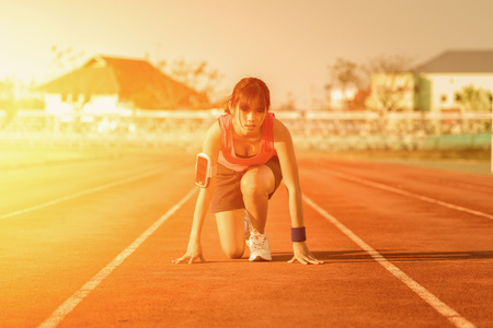 starting position: Confident young female athlete in starting position ready to start a sprint.