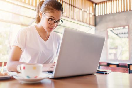 ビジネス起業家アジアの少女カフェでノート パソコンでオンラインで作業しています。ビジネスの起業家アジアの家でノート パソコンを使用します 写真素材