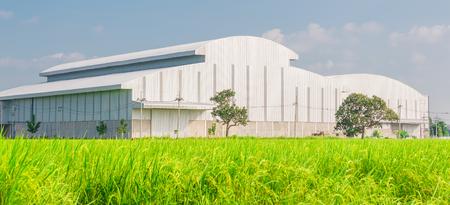 Fabrik in der Mitte eines grünen Ackerland an einem bewölkten Tag