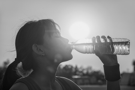 Female drinking a bottle of water , sunset , black and white