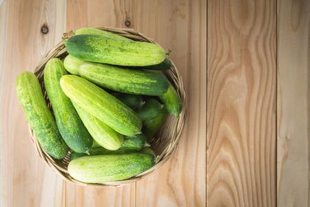 lug: Fresh cucumbers in basket on wood Stock Photo