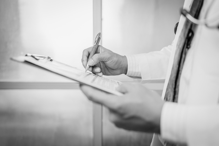 prescribing: Close-up Of Male Doctor Filling The Medical Form , black and white.