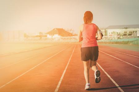 Sports woman running on tracks  , sunset , vintage tone