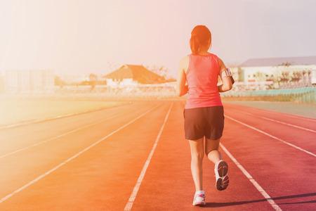 Sports woman running on tracks  , sunset