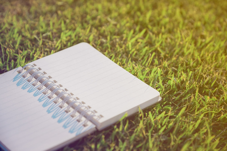 note booklet: Old notebook on fresh spring green grass , vintage tone Stock Photo