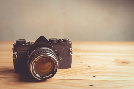 old photograph: Retro camera on wood table background , vintage tone