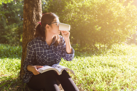 young woman reading book and drinking coffee from cup in park Stock Photo