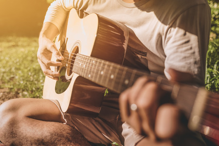Man fingers playing guitar outdoor in summer park. Musician man and her guitar in nature park, Practice guitar. vintage tone. Stock Photo