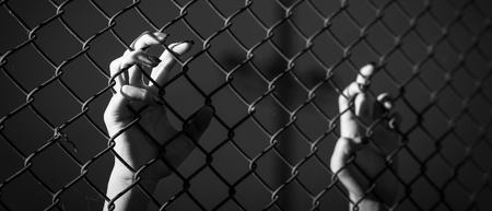 Hand holding on chain link fence. Black and white. banner panoramic crop for copy space. Imagens