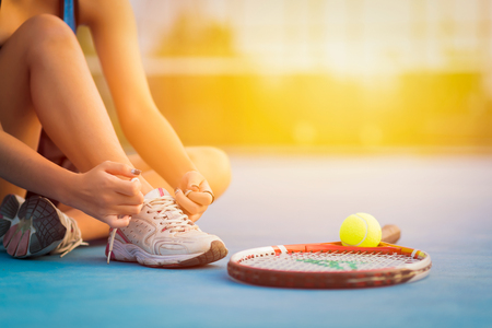 Tennis player tying shoelaces in court. sunset  Stock Photo