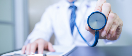 A doctor holds his stethoscope to insinuate that its time for a check up in clinic banner panoramic crop for copy space.