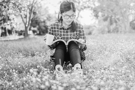 The girl sitting on a green grass with cup of coffee and reads the book, young woman  with coffee sitting on the grass and reading a book in the park black and white. Stock Photo