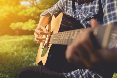 woman playing guitar at public park, womans hands playing acoustic guitar, close up.