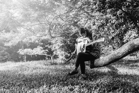 Female fingers playing guitar outdoor in summer park. Musician woman and her guitar in nature park, Practice guitar. black and white.