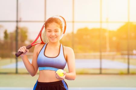 Woman in sportswear serves tennis ball.