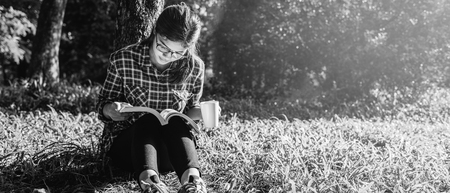 The girl sitting on a green grass with cup of coffee and reads the book, young woman  with coffee sitting on the grass and reading a book in the park black and white. banner panoramic crop for copy space.