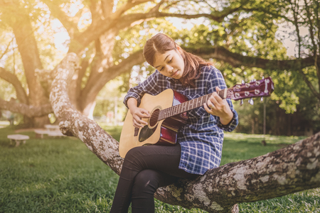 Female fingers playing guitar outdoor in summer park. Musician woman and her guitar in nature park, Practice guitar. vintage tone. Stock Photo