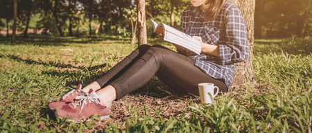 The girl sitting on a green grass with cup of coffee and reads the book, young woman  with coffee sitting on the grass and reading a book in the park vintage tone. banner panoramic crop for copy space. Stock Photo